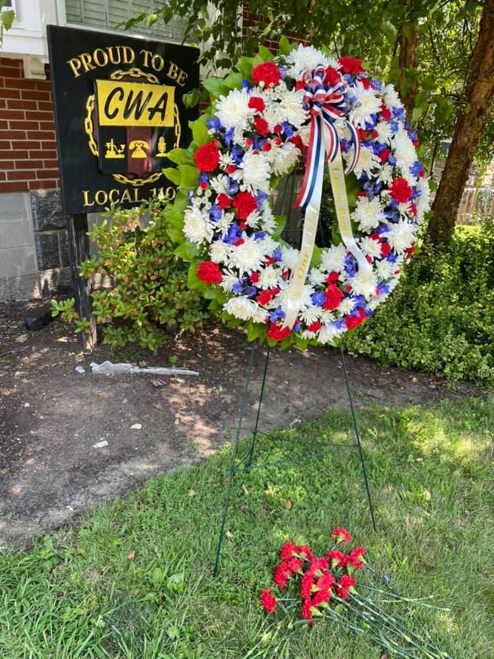 Memorial wreath in front of a CWA Local 1103 sign