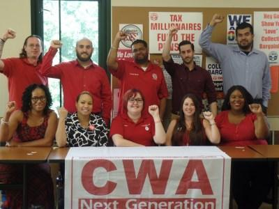 Group of CWA members at a table with a CWA Next Generation banner