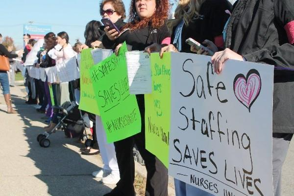 Healthcare workers with Safe Staffing signs at a rally