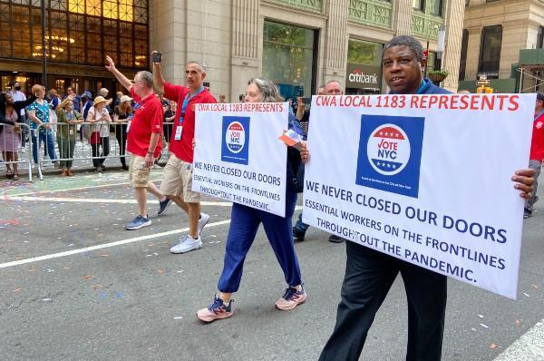 """CWA Local 1183 members march with signs saying """"we never closed our doors"""""""